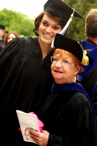 A young graduate stands with her professor for a picture.