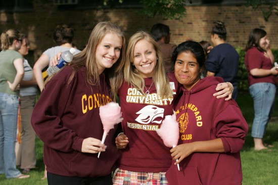 Three young women pose for a picture with cotton candy in their hands