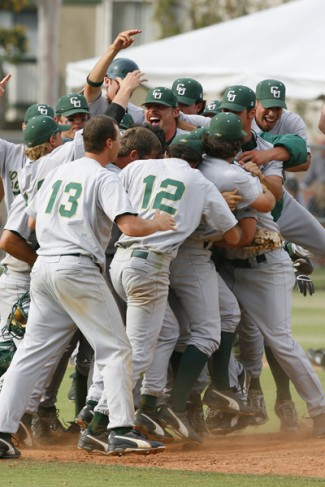 A baseball team celebrates in a huddle.