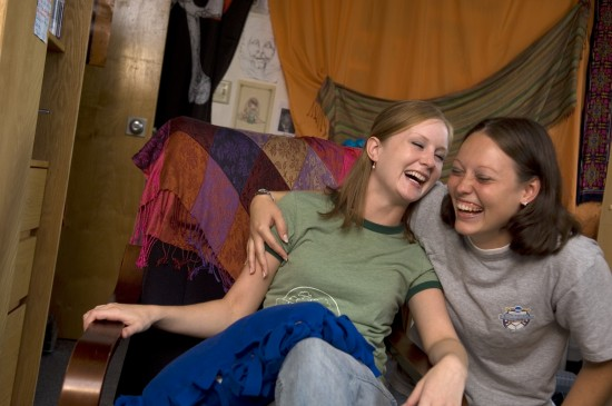 Two friends laugh together in their dorm room.