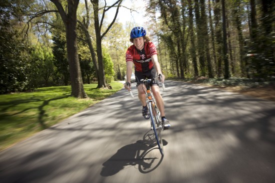 A young male biker speeds toward the camera on a nice day.