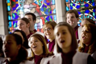 Choir sings in front of stained glass windows.