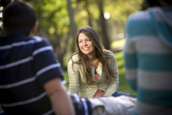 Young woman smiles as she enjoys class on the lawn.