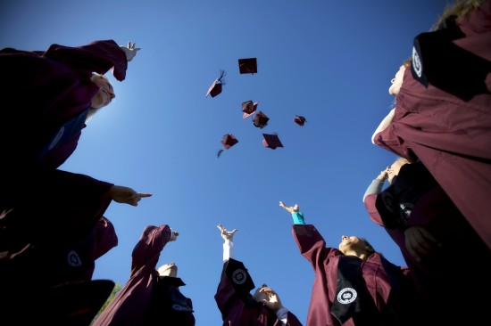 Six graduation hats float in the air above their graduates.