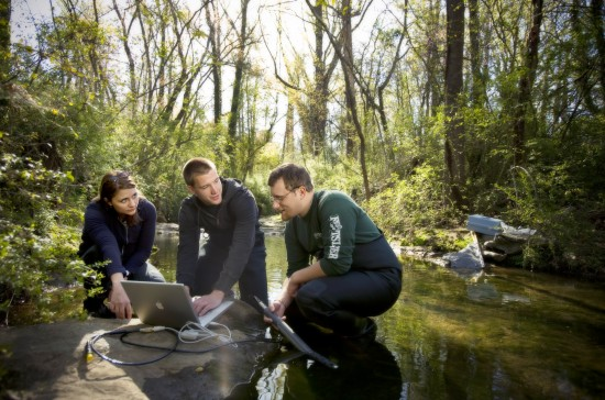 A professor and two students take water samples from a stream in a wooded area.