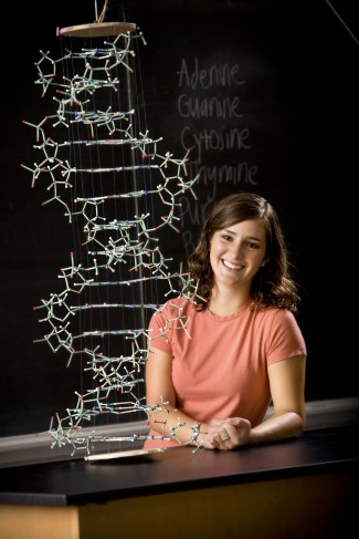A young woman poses with a model of DNA.