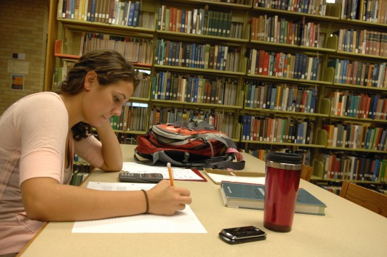 Girls writes essay in the library