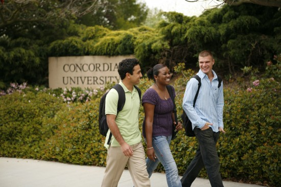 A group of students happily walks by the Concordia sign.