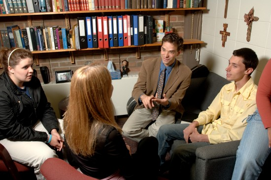 A small group of students discuss with a professor in his office.