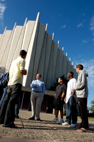 A professor explains something to a small group of students outside the chapel.
